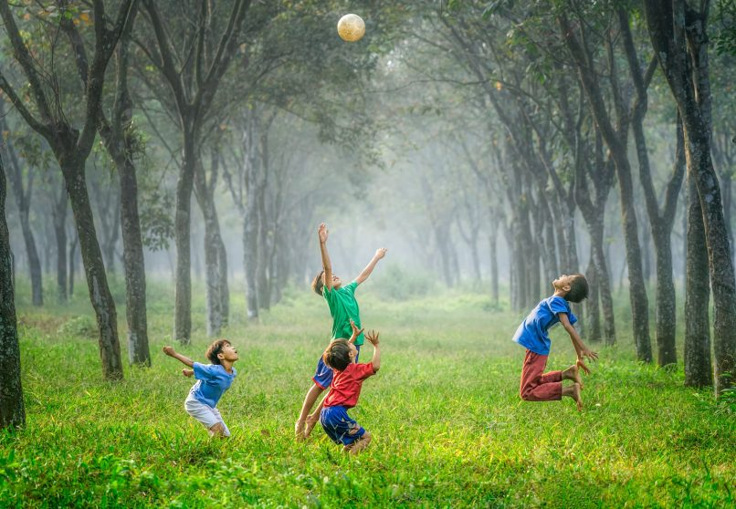 4 children playing ball in a forest. Photo by Robert Collins on Unsplash