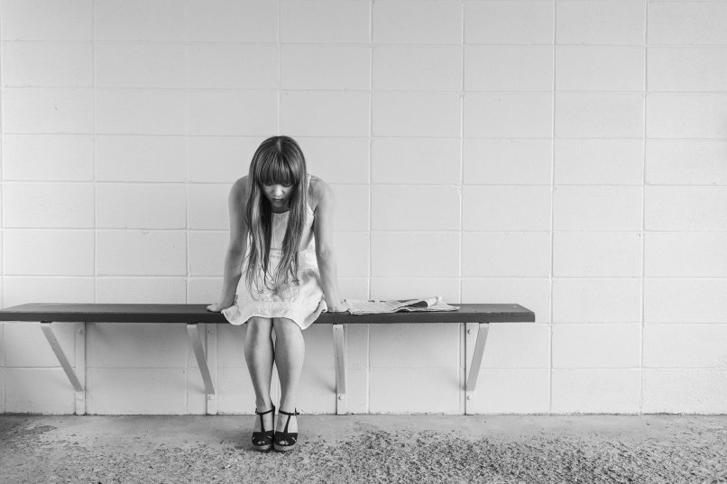 Canadian health care is broken. Photo of a woman with long hair sitting on a bench. She's wearing a dress and her head is hanging down.