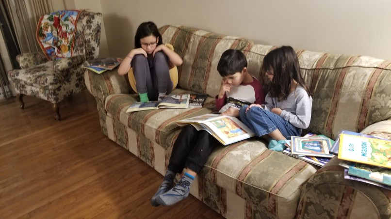 Three children reading on a couch