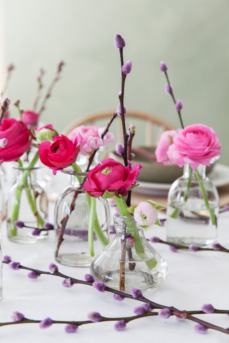 Table setting with pink ranunculus in mini vases