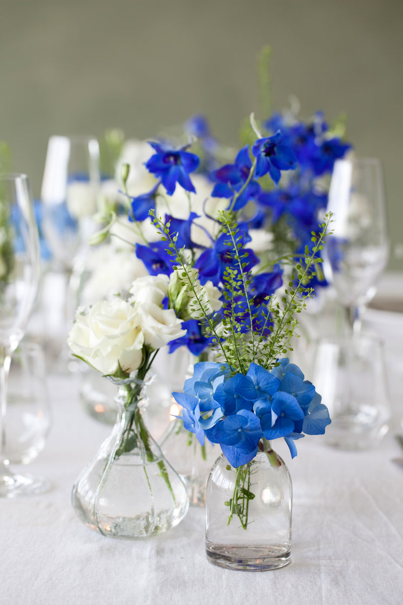 Table setting with blue flowers in vases