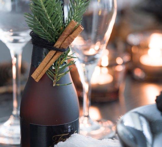 Flaske som er julepyntet og matcher julebordet