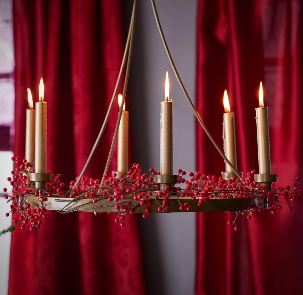 Lysekrone med levende lys og røde bær.