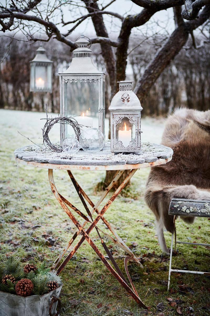 Et lite bord i hagen er pyntet med lyslykter og en krans.