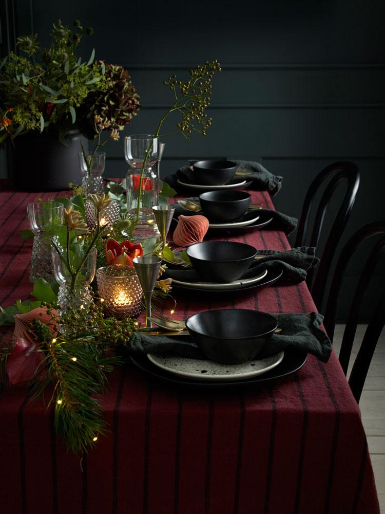 Vakkert pyntet julebord i moderne sort og klassisk rødt.