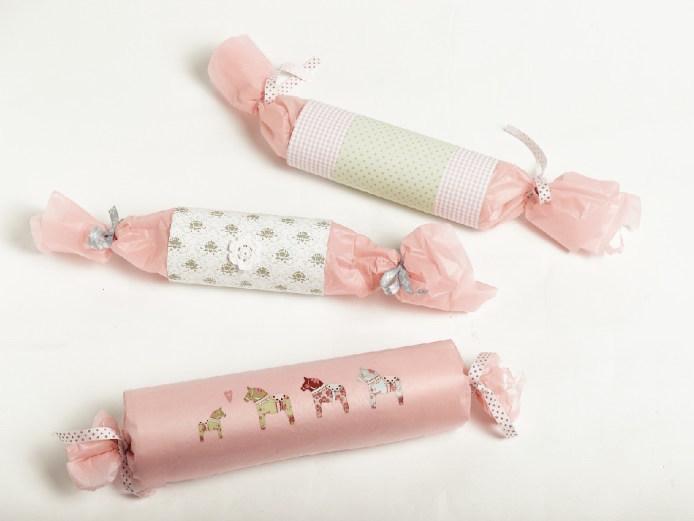 Rosa gaver pakket inn med pynt av dekorpapir, silkepapir, klistremerker og bånd.