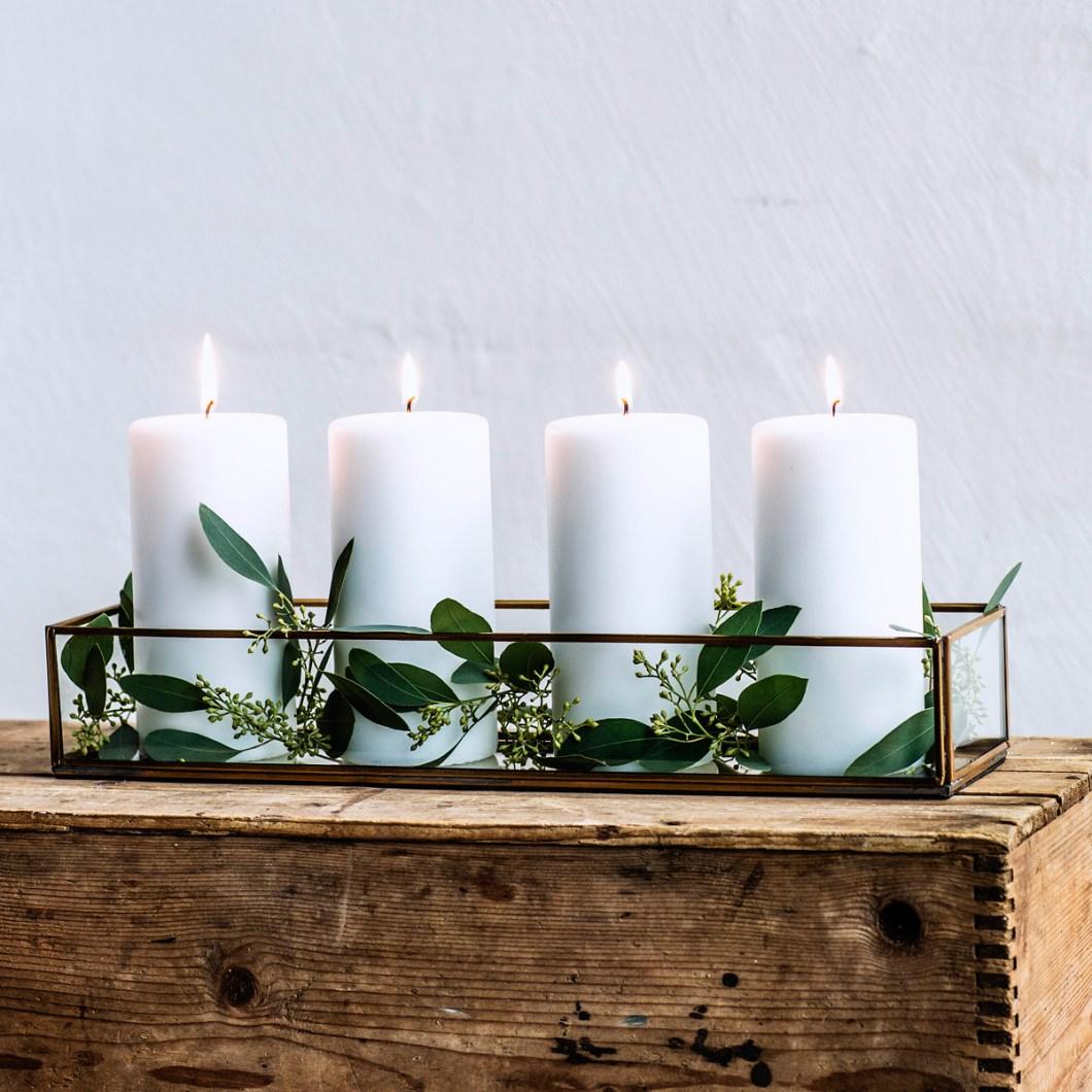 Adventsstake med kubbelys og vintergrønt.