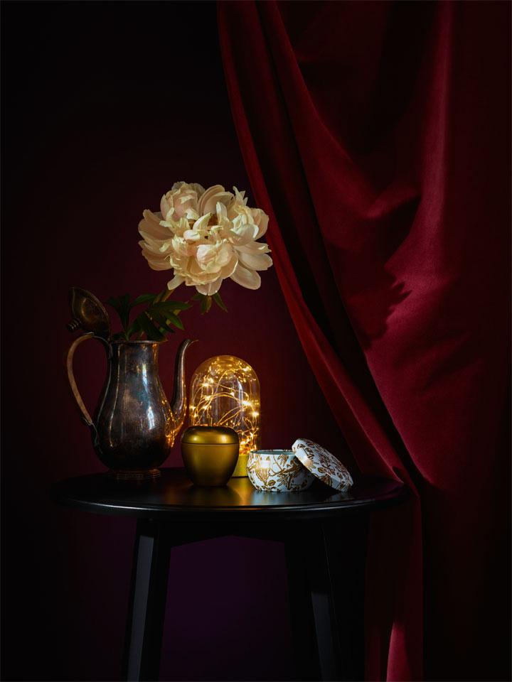 Sidebord med stilleben; vase, duftlys og glasskuppel med lyslenke.