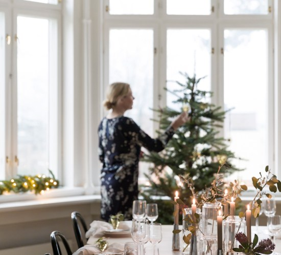 Vakkert dekket julebord og juletre pyntet til julefest.