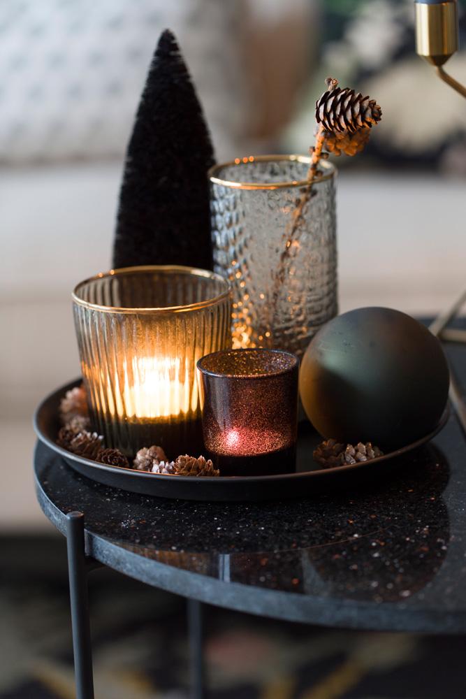 Et brett med en vase, en julekule og ulike telys.