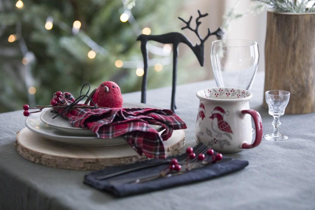 Julebord/kuvert dekket i klassisk stil, med dompap, rødrutet serviett og et reinsdyr.