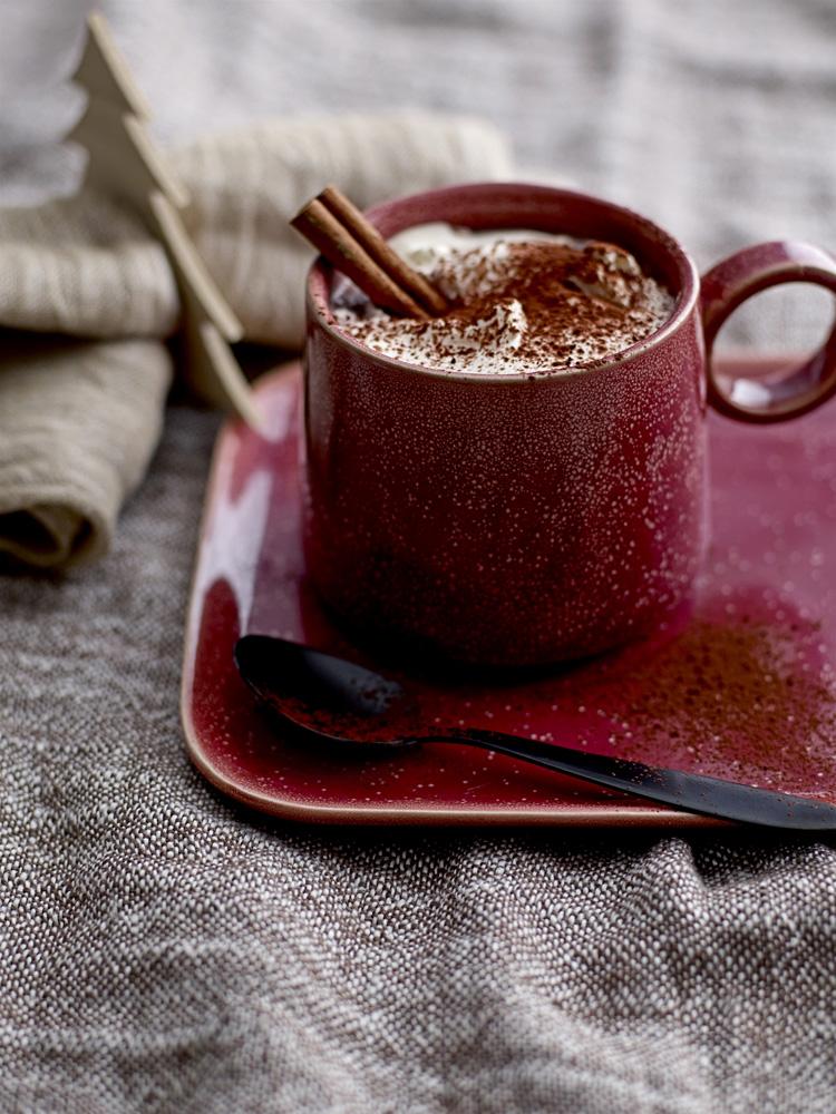 Krus med kakao og kanelstenger.