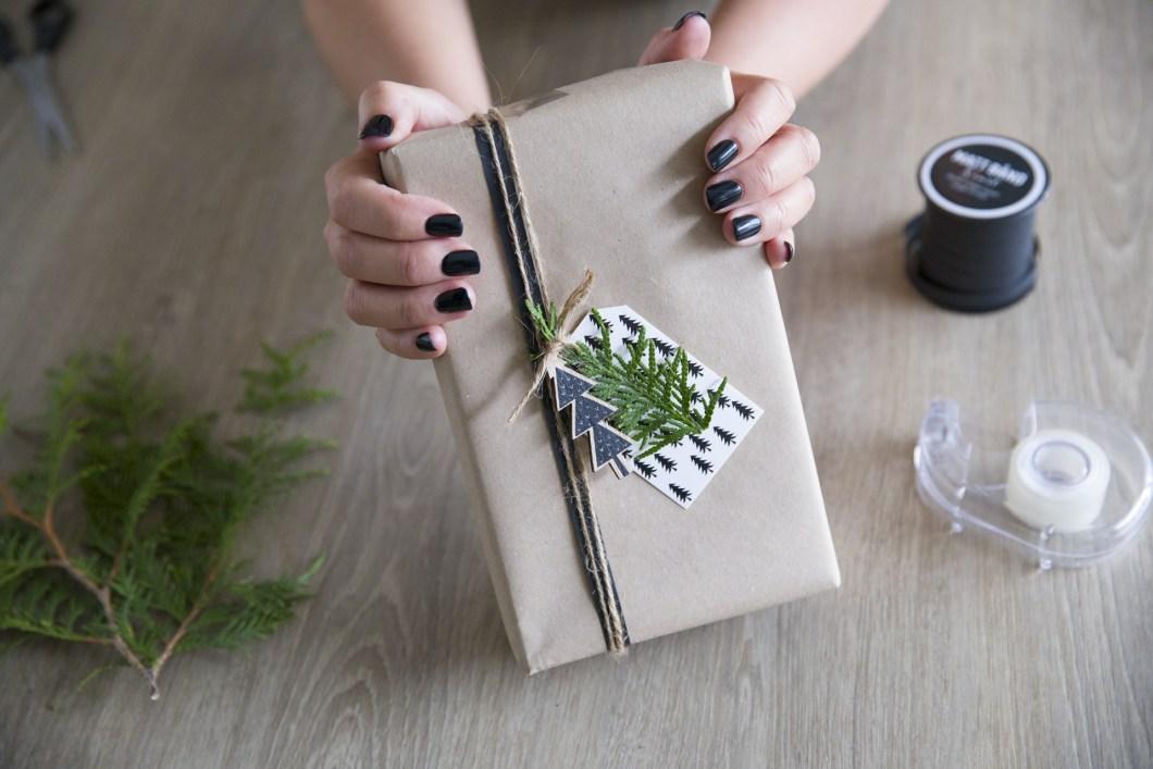 Kreativ innpakking av julegave med hyssing, juletrepynt og til-og-fra-kort.