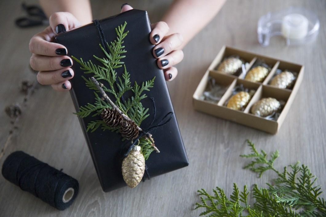 Kreativ innpakking av julegave med tuja, kvist og juletrepynt