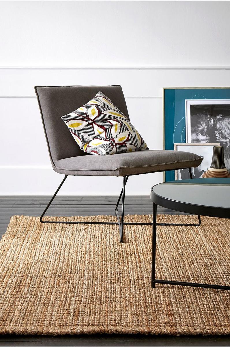 Stuemiljø med moderne møbler og teppe av jute.