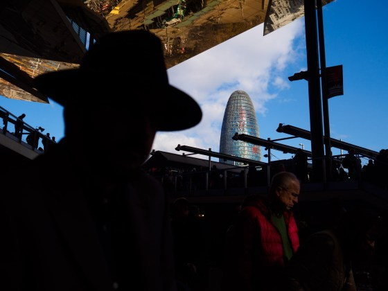 Men looking at antiques in the flea market Els Encants, with the Agbar tower behind