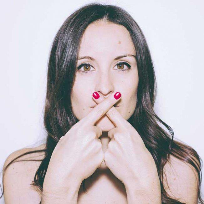 Femme qui met ses doigts manucurés croisés sur la bouche
