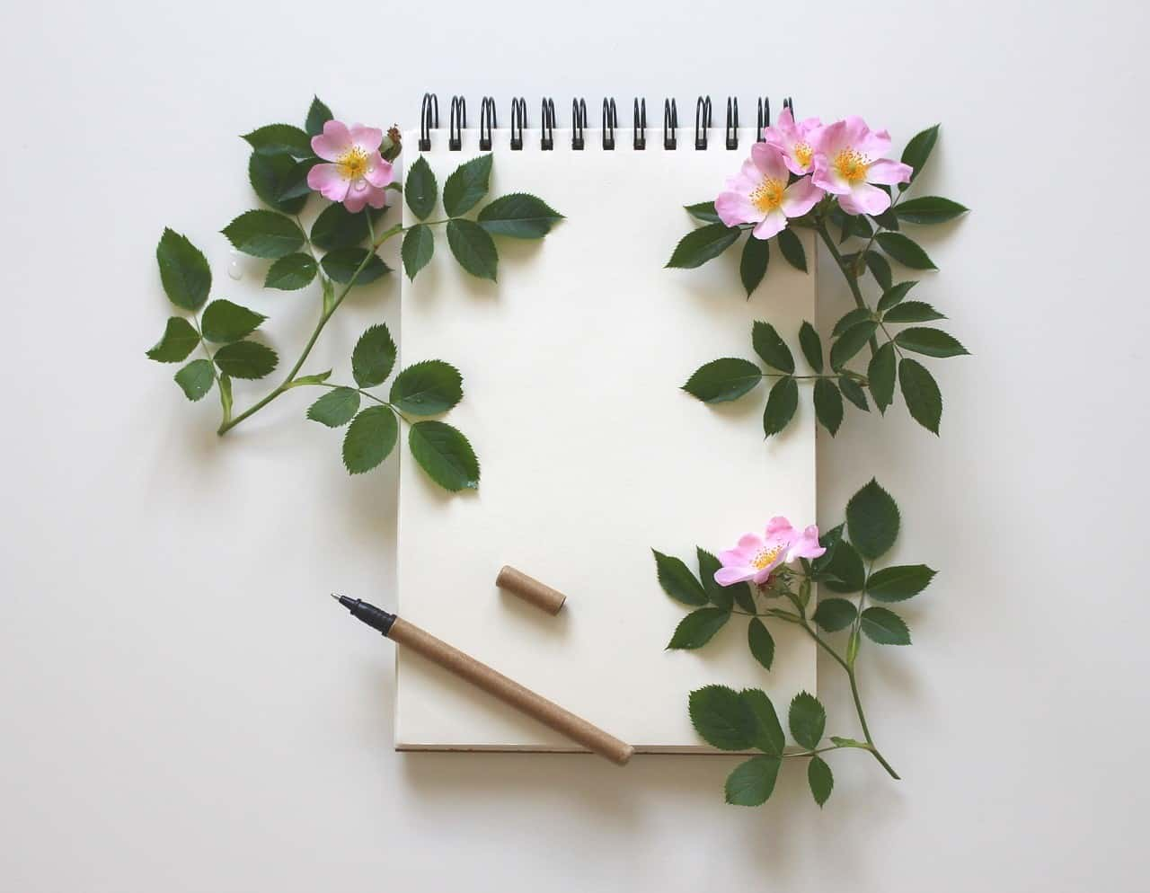 Writing with roses on a notepad