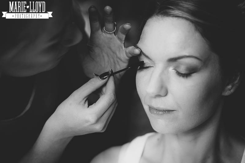 Black and white photograph of bride getting the final touches to her makeup