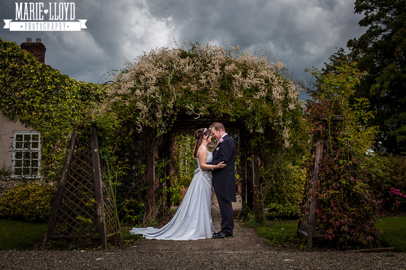 The beautiful arch in bloom at Rossett Hall, with a moody dark sky over the bride and groom.