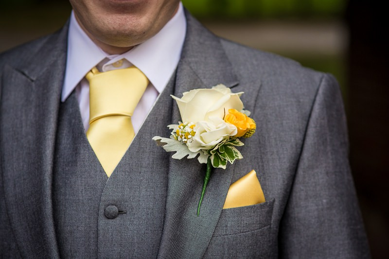 Groom with yellow tie and buttonhole on grey suit