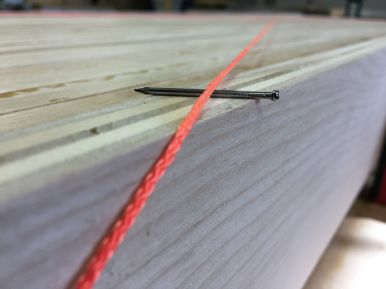 Small nails offset one string by its diameter