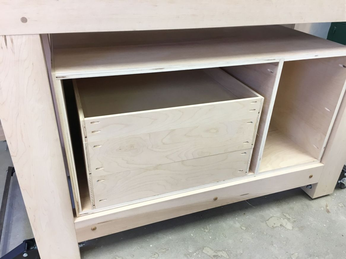 Three drawer boxes stacked in workbench cabinet