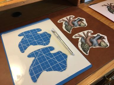 Cutting out the finished vinyl graphics with a No. 11 blade and cutting mat