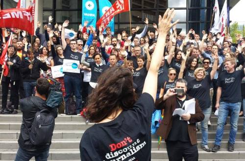 Workers in black t-shirts outside a Fairfax building with flags protesting job cuts and the takeover by channel nine as part of the union MEAA's campaign.