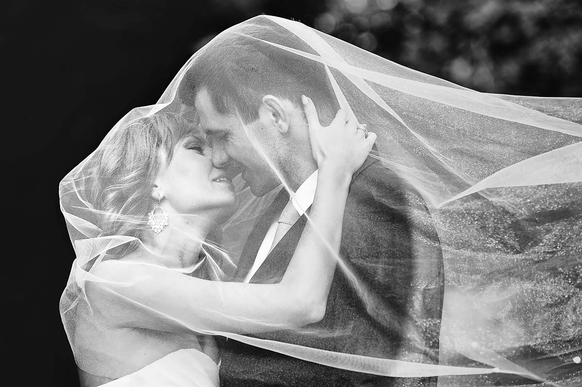 under the veil, wedding couple kissing, wedding day on location shot