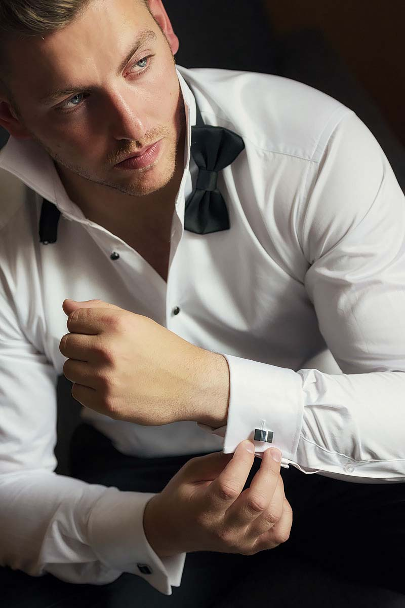 groom is getting ready, holding cufflinks