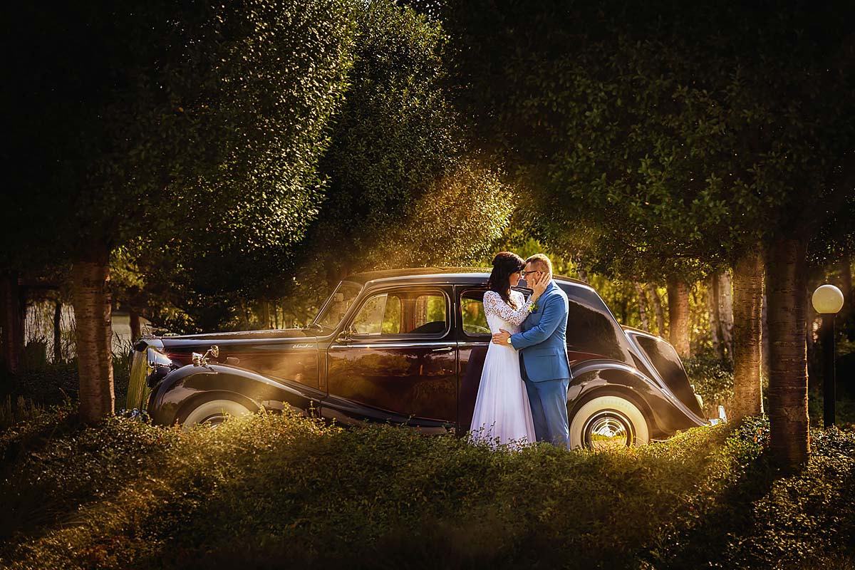 sun rays, wedding couple in front of the antique car