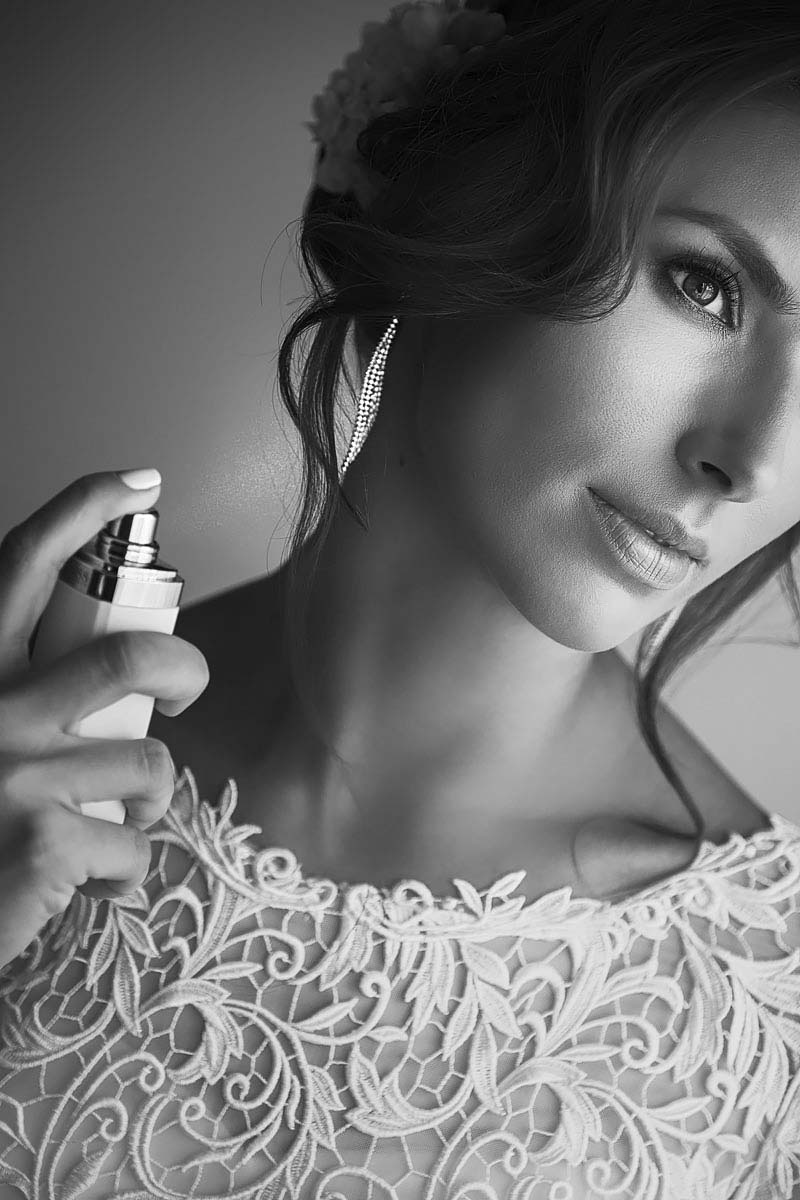 black and white portrait of the bride, spraying perfume