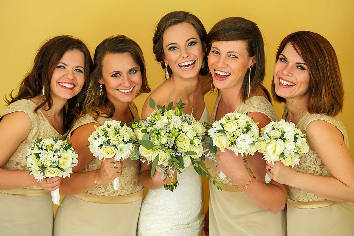 portrait, bride with bridesmaids giggling, flowers