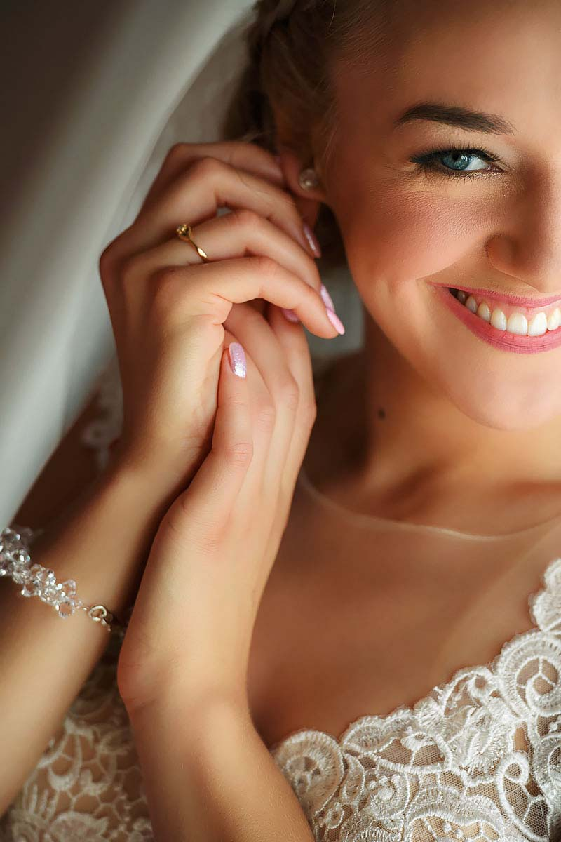 portrait of the gorgeous bride, holding earring