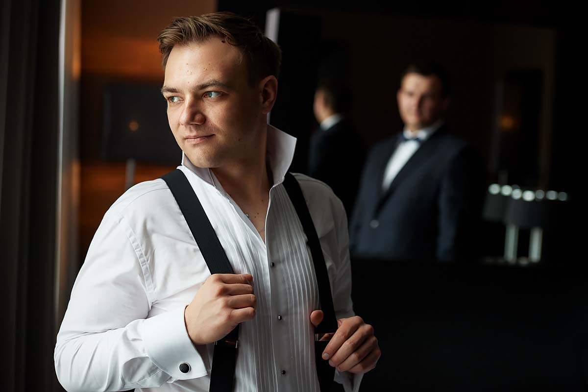 groom getting ready, suspenders, gallows, pair of braces, best men in the background