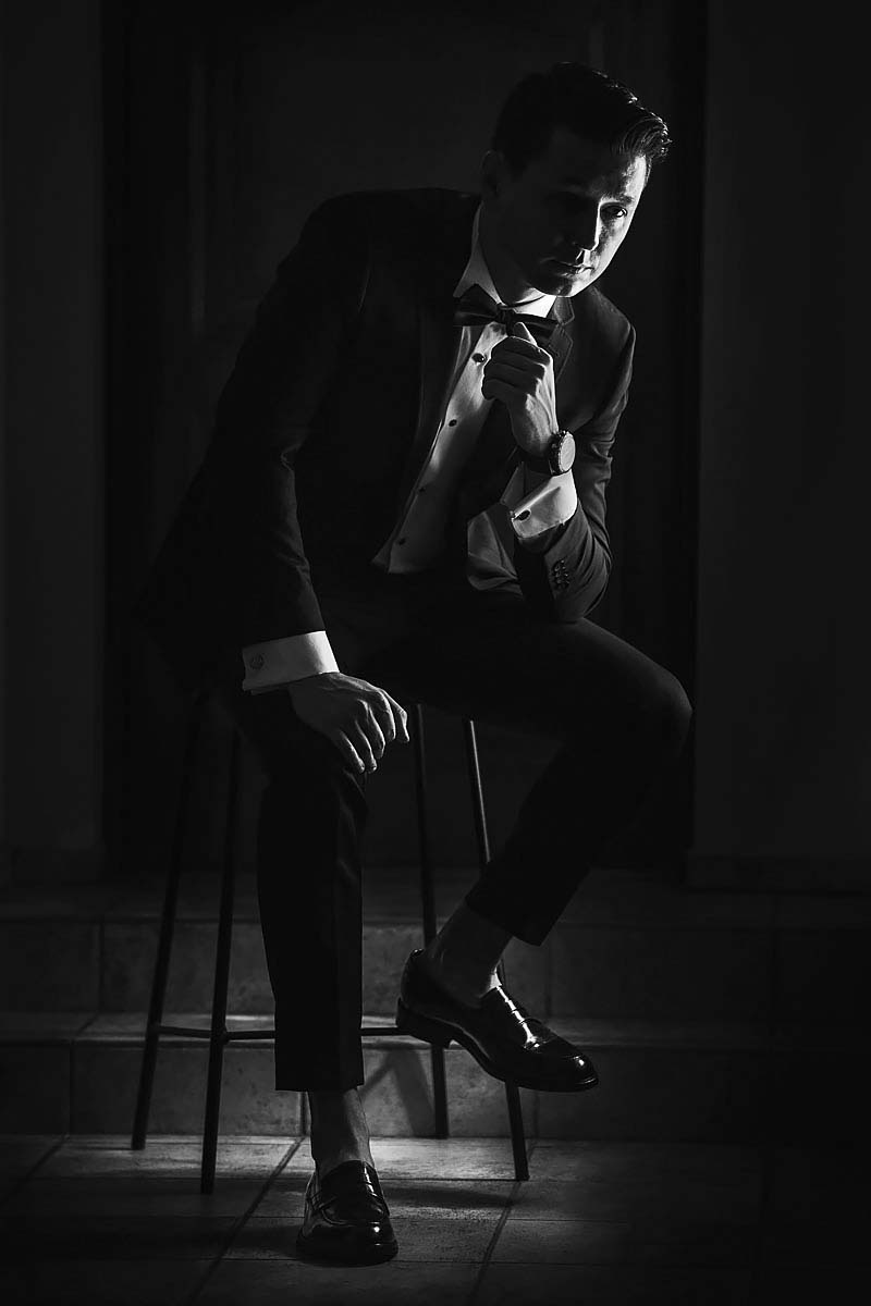the groom is sitting on the chair, black and white