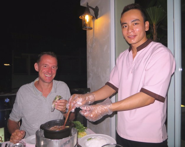 One of the things we love about traveling is the occasional mystery of just what we're going to get. Here our friendly waiter is showing Mark how to wrap the various ingredients he's been served into a Vietnamese dish.