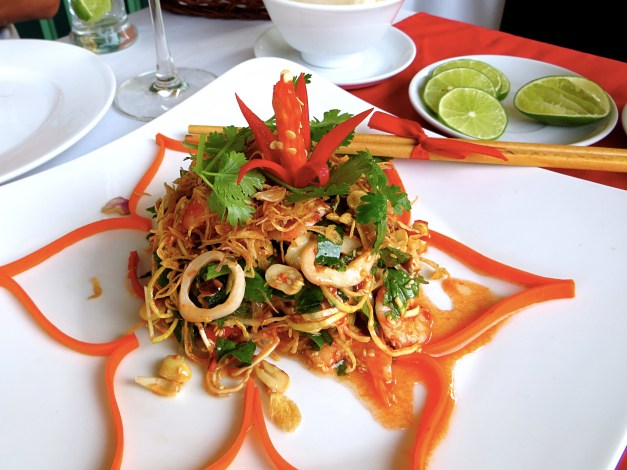 A Banana Blossom salad, surrounded by a carrot garnish, remarkably cut in one single piece