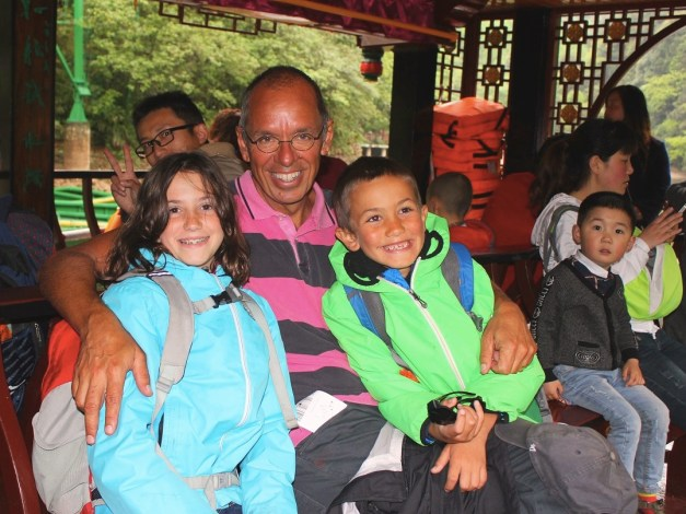 Sierra and Jacob with their uncle on a little boat across a little lake on Qingcheng