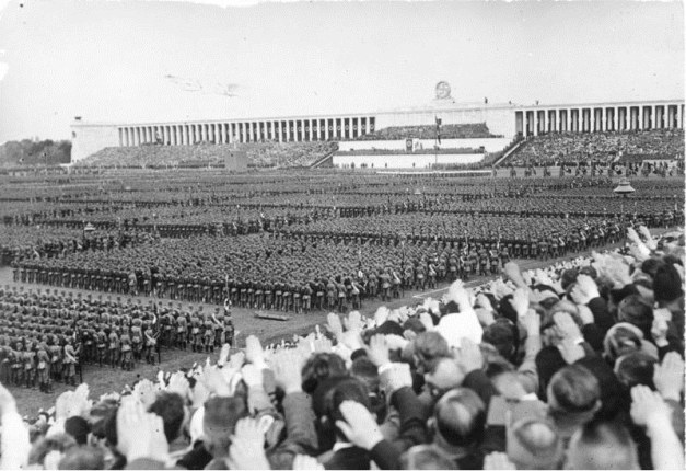 The crowd looks toward the Führer's box at the center of the insanity at the Nuremberg Parade Ground