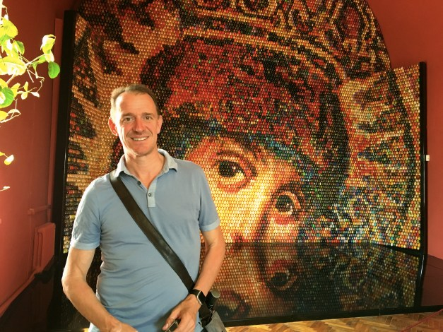"""Mark in front of a mosaic titled  """"Looking Into Eternity """" by Ukrainian artist Oksana Mas, displayed in a museum on the grounds of St. Sophia. It's made from 15,000 individually painted Easter eggs."""