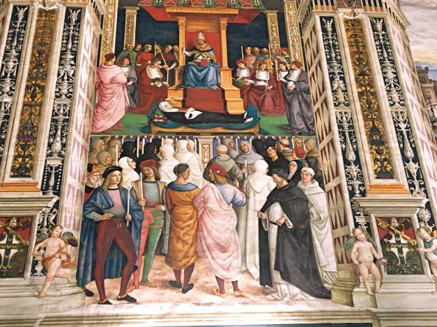 The canonization of St. Catherine of Siena, one of the frescoes in the Piccolomini Library (presumably before she was beheaded). The character in red tights in the lower left was Raphael, who was a young assistant to the primary painter Pintorichio, standing to his left.