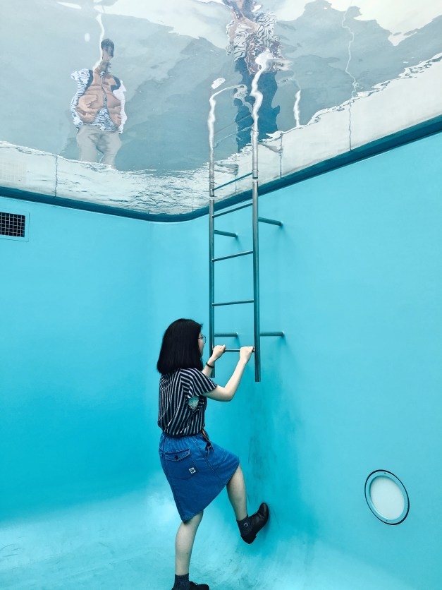 """The modern art museum included Leandro Erlich's """"The Swimming Pool"""". From inside you go downstairs and walk in, seeing a layer of water above you. This is an actual woman, pretending to climb the ladder while her boyfriend (and Mark) was taking a picture."""
