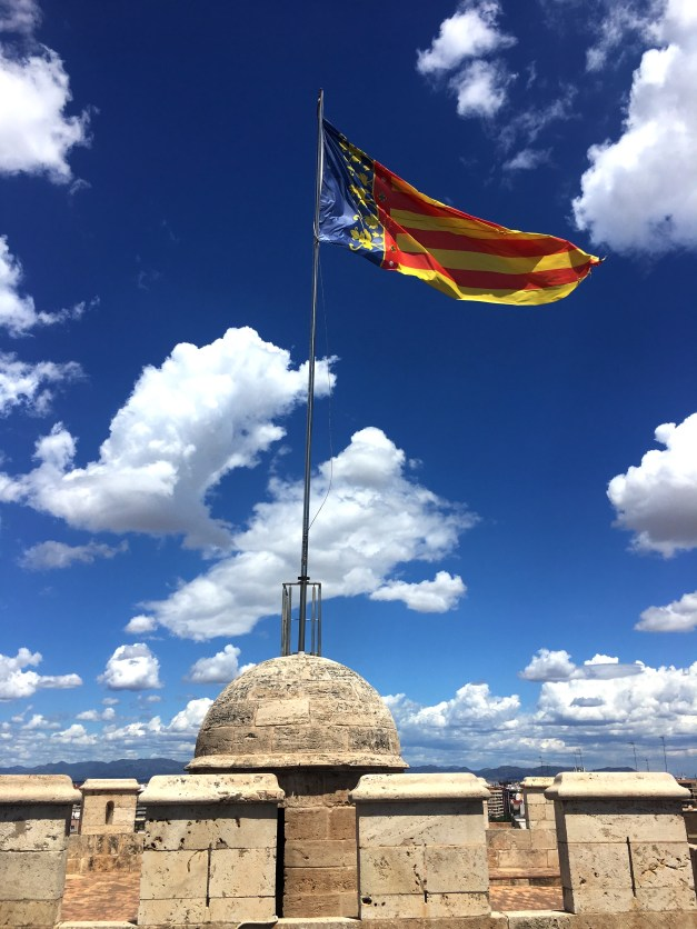 A flag blowing from atop the Torres de Quart, one of several ancient towers still standing in València
