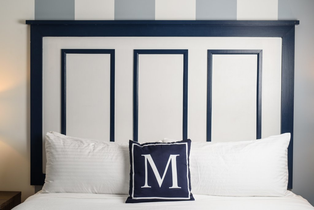 Queen Bed with white sheet and blue pillow.
