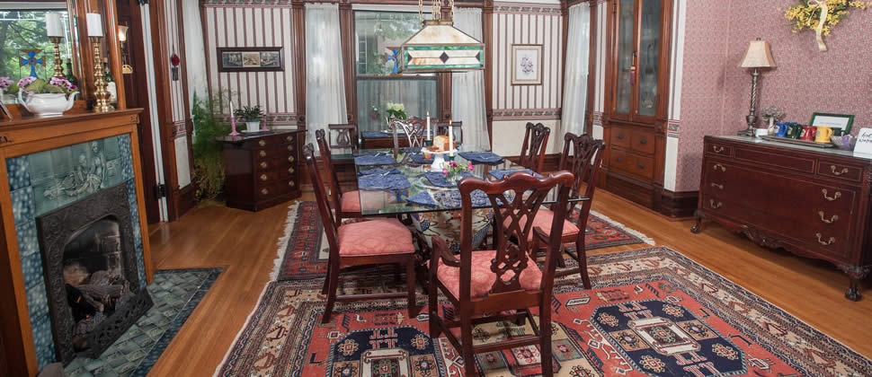 Dining room with glass table set up for Breakfast with 6 chairs and a gas fireplace