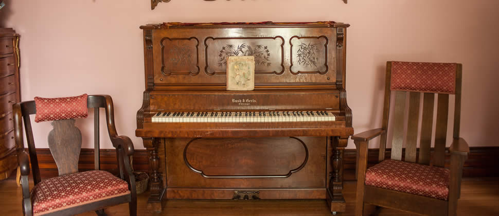 Old fashion piano with two chairs on each side