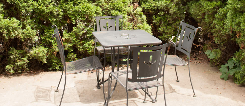 Metal table and 4 chairs in a court yard with greenery all around