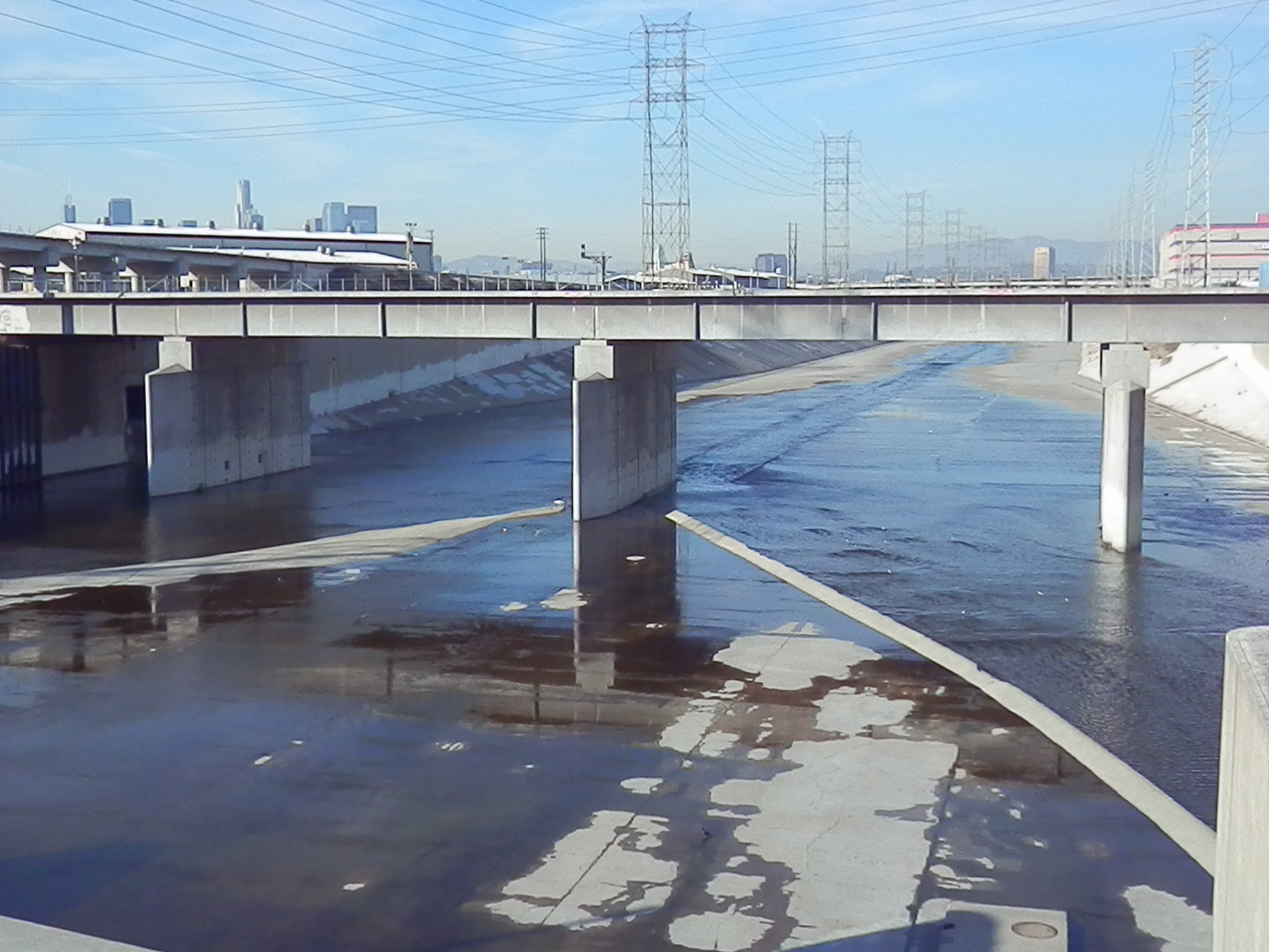 (An image of the water-less Los Angeles River, with the downtown skyline in the background. The city has been trying in vain to revive the riverfront for decades. / photo by Scott Beyer)